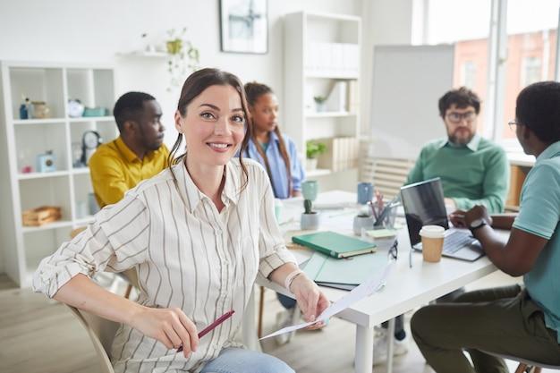 Portret van lachende jonge vrouw zittend aan tafel tijdens ontmoeting met creatieve business team