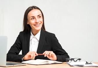 Portret van lachende jonge vrouw zittend op de werk plek weg te kijken