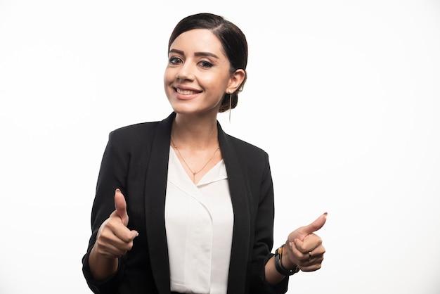 Portret van lachende jonge zakenvrouw duimen opdagen.