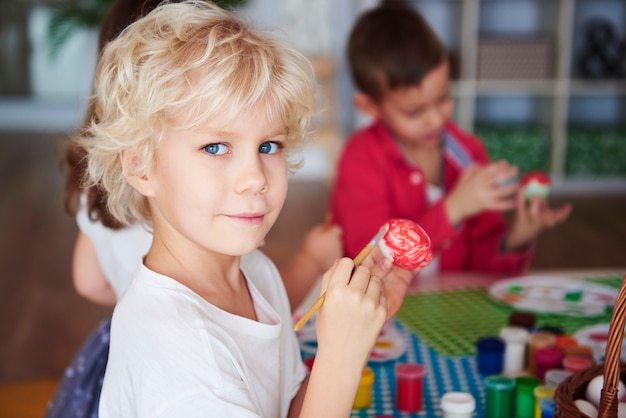 Portret van lachende jongen die paaseieren schildert