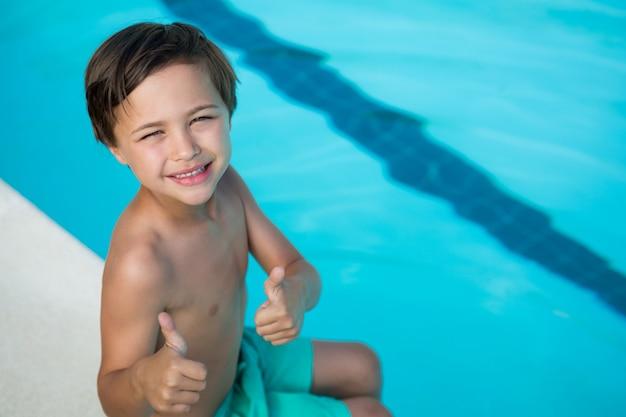 Portret van lachende jongen duimen opdagen bij het zwembad