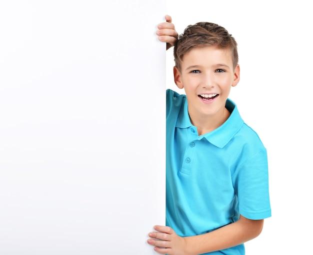 Portret van lachende jongen kijkt uit van wit bordje geïsoleerd op wit