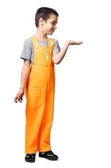 Portret van lachende jongen timmerman in oranje werk overall demonstreert met de hand en kijkt naar haar, plezier op witte geïsoleerde achtergrond