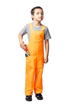 Portret van lachende jongen timmerman in oranje werk overall poseren op witte geïsoleerde achtergrond.