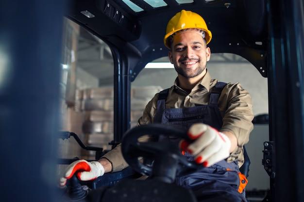 Portret van lachende kaukasische heftruckchauffeur rijden machine en werken in pakhuis.