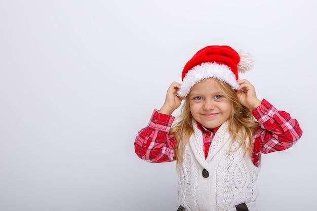 Portret van lachende kleine blonde meisje in santa hoed op witte achtergronden