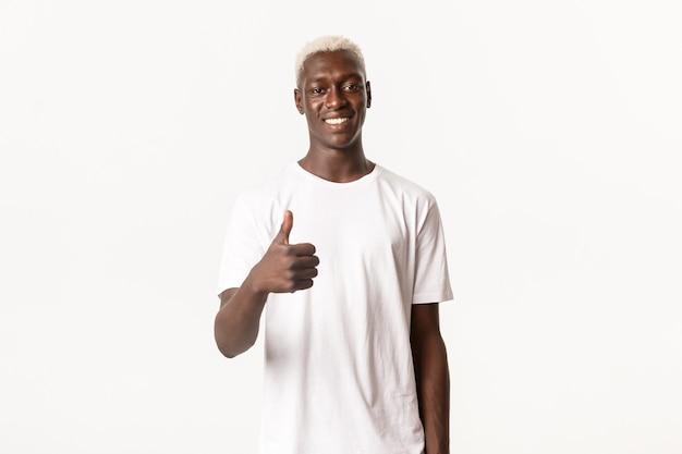 Portret van lachende knappe afro-amerikaanse man duim-up in goedkeuring, als iets goeds tonen
