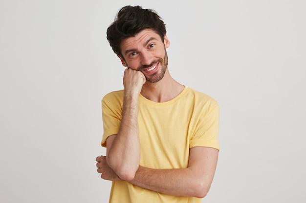 Portret van lachende knappe bebaarde jonge man draagt gele t-shirt ziet er gelukkig uit en houdt de handen gevouwen geïsoleerd op wit