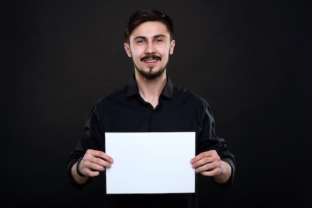 Portret van lachende knappe jonge bebaarde man in zwart shirt met blanco papier in handen tegen donkere achtergrond