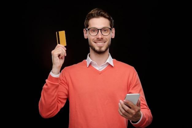 Portret van lachende knappe jongeman in bril met behulp van smartphone-app tijdens het controleren van het saldo van de creditcard