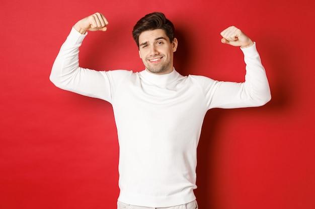 Portret van lachende knappe man in witte trui die biceps buigt en opschept met kracht opschepper...