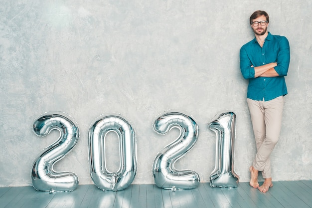 Portret van lachende knappe man poseren in de buurt van muur. sexy bebaarde man staand in de buurt van silver 2021-ballonnen. gelukkig nieuw 2021 jaar. metalen cijfers 2021