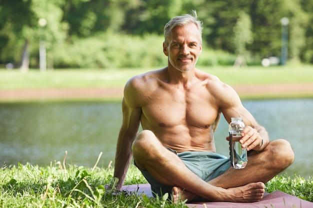 Portret van lachende knappe volwassen sportman zittend met gekruiste benen op de mat en drinkwater tijdens het rusten aan de rivier