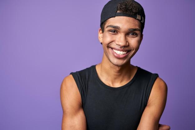 Portret van lachende latino transgender man in zwarte tshirt en pet op paarse achtergrond