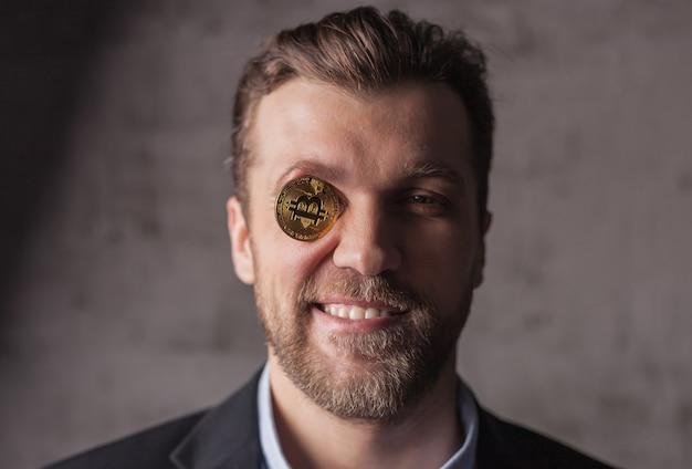 Portret van lachende man met bitcoin in plaats van oog