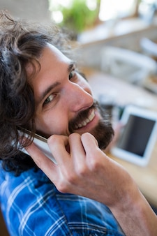 Portret van lachende man praten over de mobiele telefoon in de koffiebar