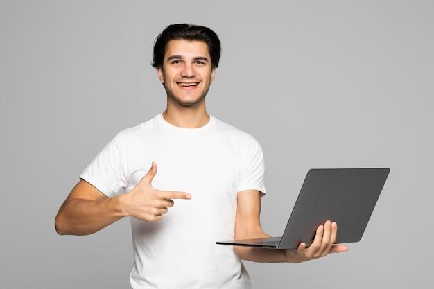 Portret van lachende man wijzend op laptop met leeg scherm geïsoleerd op wit