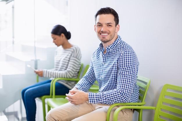Portret van lachende man zittend op een stoel