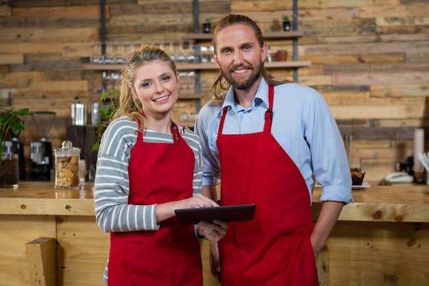 Portret van lachende mannelijke en vrouwelijke barista's met behulp van digitale tablet in coffeeshop