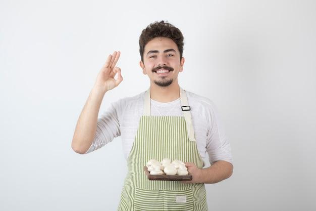 Portret van lachende mannelijke kok die rauwe champignons op wit houdt