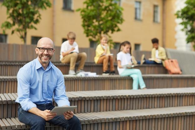 Portret van lachende mannelijke leraar camera kijken terwijl digitale tablet zittend op de bank buiten met groep schoolkinderen in achtergrond, kopie ruimte