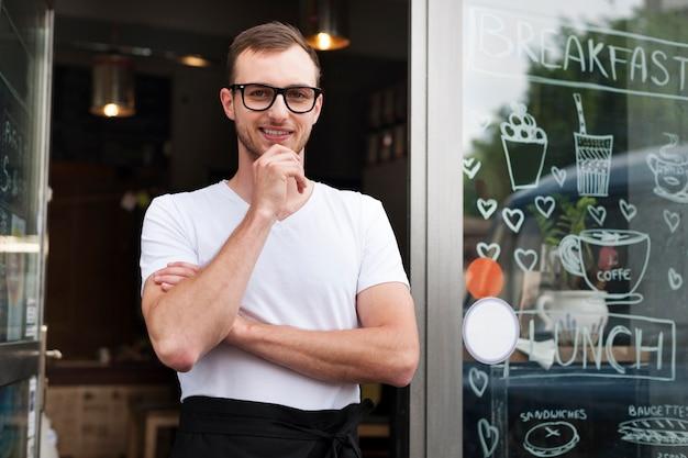 Portret van lachende mannelijke ober buiten het café