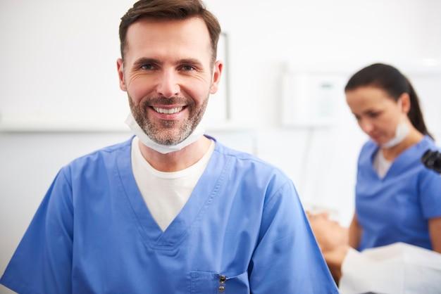 Portret van lachende mannelijke tandarts in de tandartskliniek