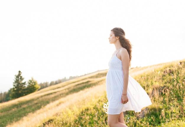 Portret van lachende meisje met boeket van wilde bloemen in een veld met groen gras en blauwe hemel.