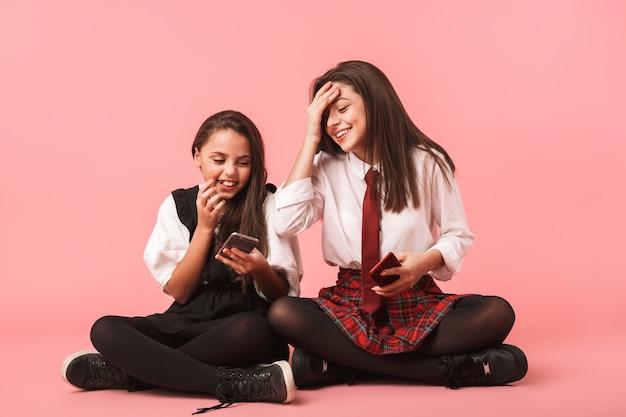 Portret van lachende meisjes in schooluniform met behulp van mobiele telefoons, zittend op de vloer geïsoleerd over rode muur