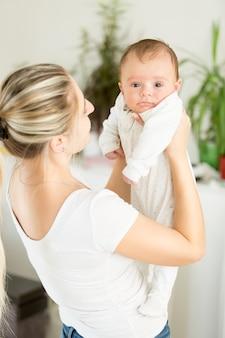 Portret van lachende moeder die haar babyjongen vasthoudt