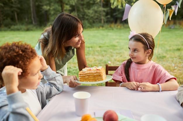 Portret van lachende moeder die verjaardagstaart naar klein meisje brengt tijdens verjaardagsfeestje buitenshuis kopiëren...