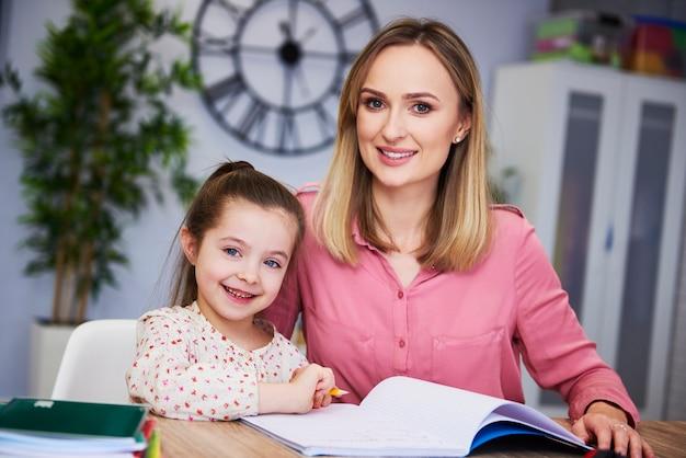Portret van lachende moeder en kind die thuis huiswerk maken