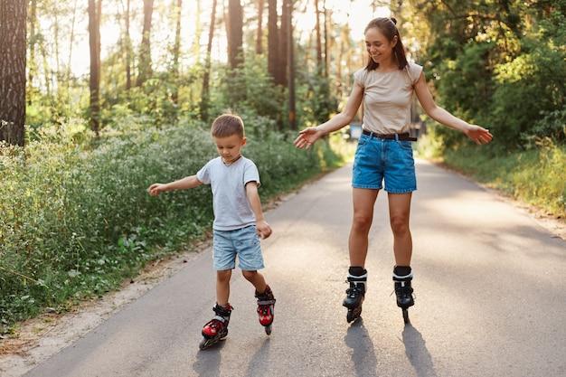 Portret van lachende moeder en zoon leren rolschaatsen, moeder met kind die samen plezier heeft op rolschaatsen in het zomerpark, geconcentreerd kind skaten, mama verheugt zich over zijn succes.