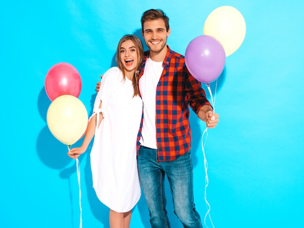 Portret van lachende mooi meisje en haar knappe vriendje bedrijf bos van kleurrijke ballonnen en lachen. gelukkige verliefde paar. fijne verjaardag
