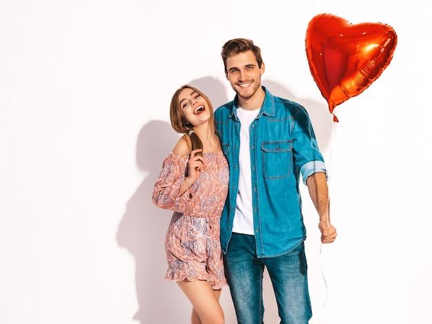 Portret van lachende mooi meisje en haar knappe vriendje houden hartvormige ballonnen en lachen. gelukkige verliefde paar. fijne valentijnsdag