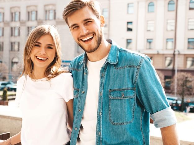 Portret van lachende mooi meisje en haar knappe vriendje in casual zomer kleding. . knuffelen