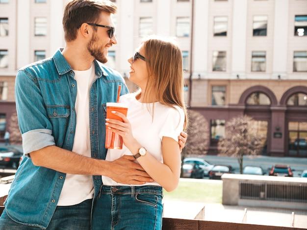Portret van lachende mooi meisje en haar knappe vriendje in casual zomer kleding. . vrouw met fles water en stro