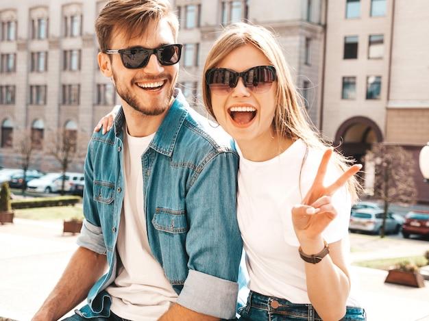 Portret van lachende mooi meisje en haar knappe vriendje. vrouw in casual zomer jeans kleding. . toont vredesteken