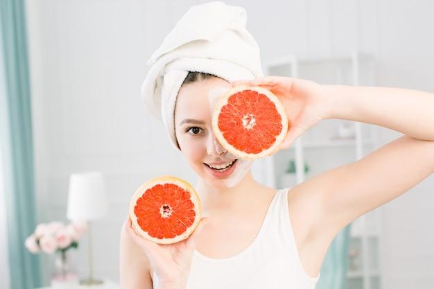 Portret van lachende mooi meisje met witte handdoek op het hoofd met helften van grapefruits in de buurt van gezicht één oog sluiten, gezonde perfecte gladde huid, wit masker op de ene helft van het gezicht, over lichte ruimte