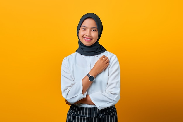Portret van lachende mooie aziatische vrouw die hijab draagt op gele achtergrond