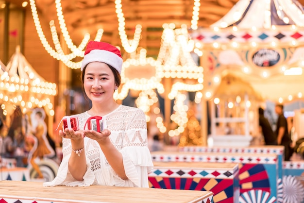 Portret van lachende mooie jonge aziatische vrouw met cadeau op de feestelijke kerstmarkt