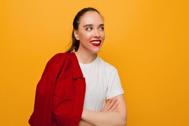Portret van lachende mooie jonge dame met een gezonde huid, rode lippen en verzameld haar speels opzoeken op geïsoleerde muur, plaats voor tekst