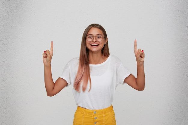 Portret van lachende mooie jonge vrouw draagt t-shirt, gele rok en bril voelt zich gelukkig en wijst naar copyspace met beide handen geïsoleerd over witte muur