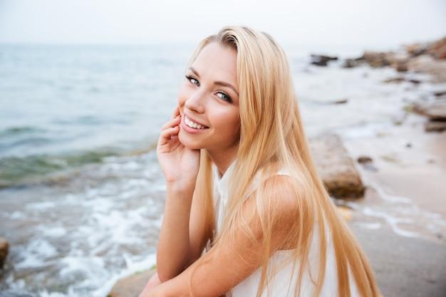 Portret van lachende mooie jonge vrouw op het strand