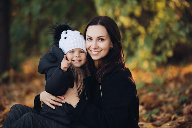 Portret van lachende mooie moeder met haar schattige dochtertje zitten in de herfst park. ouderschap concept