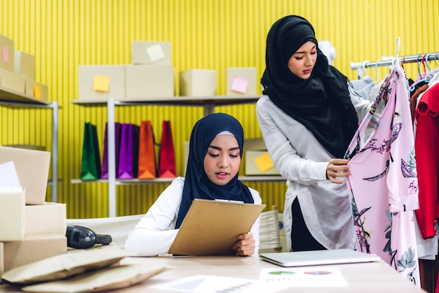 Portret van lachende mooie twee moslim eigenaar aziatische vrouw freelancer kmo bedrijf online winkelen werken op laptopcomputer met pakketdoos op tafel thuis - business online verzending en levering