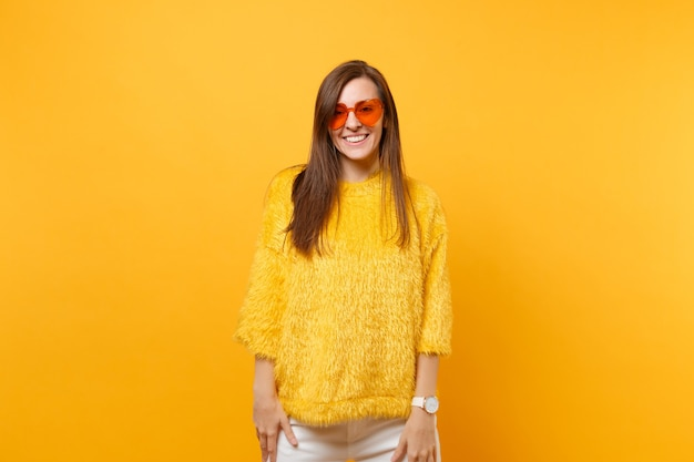 Portret van lachende mooie vrolijke jonge vrouw in bont trui en hart oranje bril staande geïsoleerd op felgele achtergrond. mensen oprechte emoties levensstijl concept. reclame gebied.