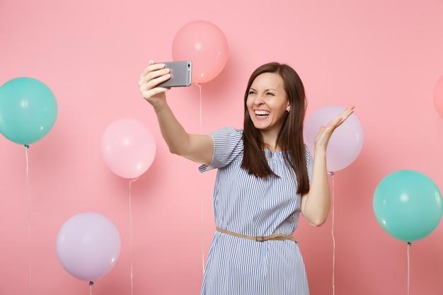 Portret van lachende mooie vrouw in blauwe jurk die selfie op mobiele telefoon doet die handen op roze achtergrond met kleurrijke luchtballons uitspreidt. verjaardagsfeestje, mensen oprechte emoties concept.