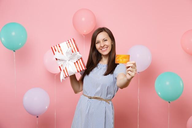 Portret van lachende mooie vrouw in blauwe jurk met creditcard en rode doos met cadeau aanwezig op pastelroze achtergrond met kleurrijke luchtballonnen. verjaardagsfeestje, oprechte emoties van mensen.