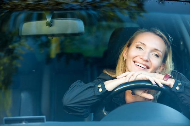 Portret van lachende mooie vrouw in de nieuwe auto - buitenshuis